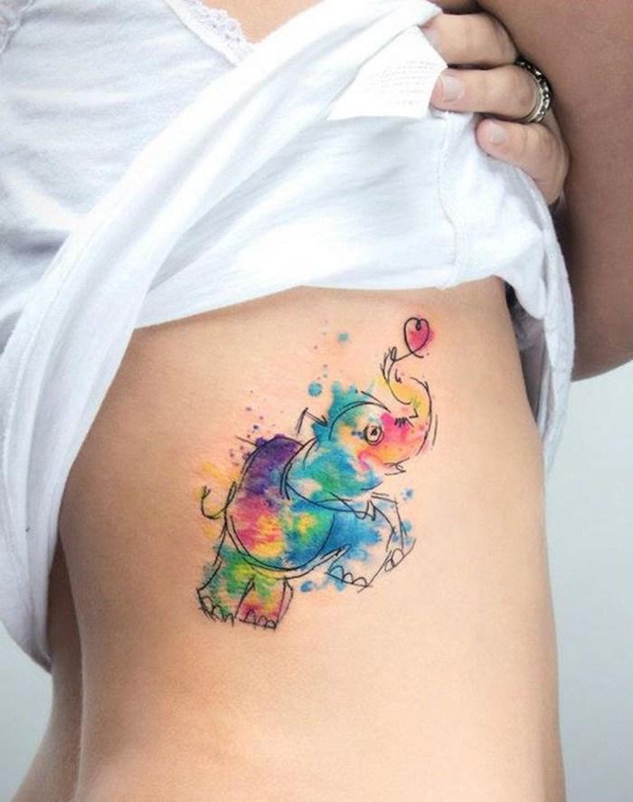 Tatuagem feminina na costela aquarela