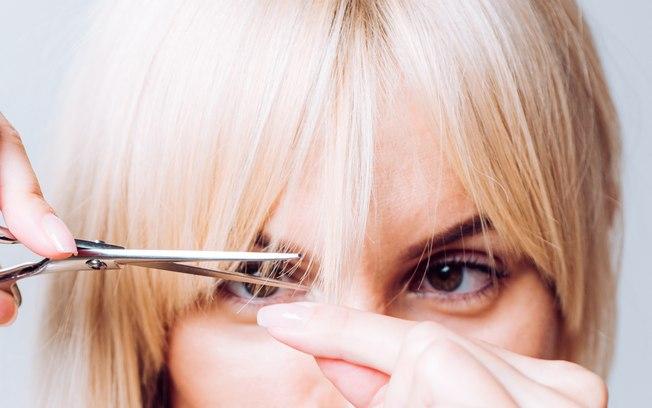 mulher cortando franja com tesoura